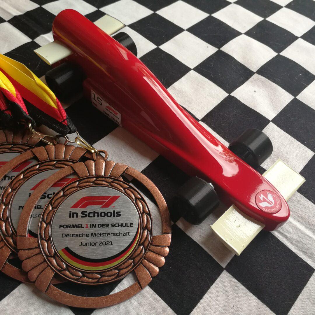 Bronzemedaille und Fahrzeug auf Zielflagge